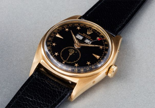 """An extremely rare, highly attractive and important yellow gold triple calendar wristwatch with moonphases, and black lacquer """"star-dial"""""""