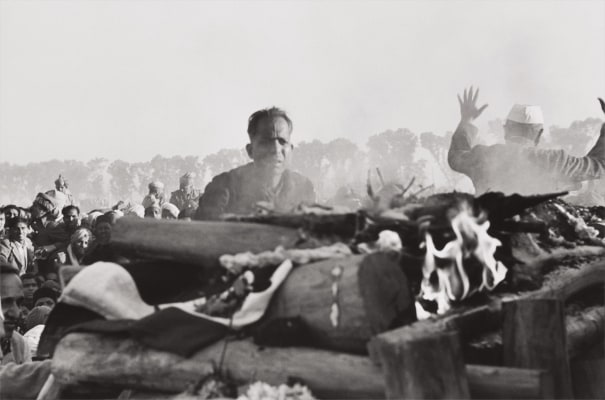 Gandhi's secretary watches the first flames of the funeral pyre, Delhi, India