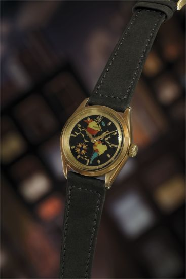 An exquisite, incredibly fine and highly attractive 14K yellow gold wristwatch with cloisonné enamel dial depicting North and South America.