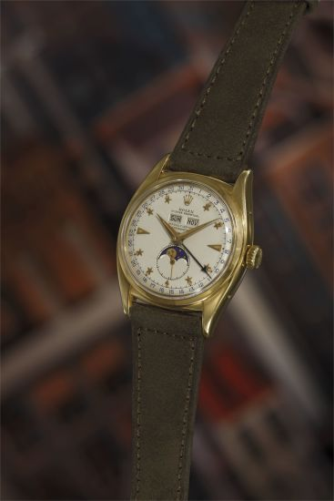 An extremely fine, rare, and important yellow gold triple calendar wristwatch with star dial, moon phase indication and bracelet.