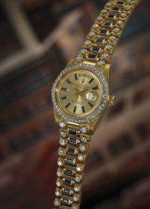 RolexAn extremely rare, important, and impressive yellow gold, diamond and baguette sapphire-set calendar wristwatch with center seconds and bracelet.