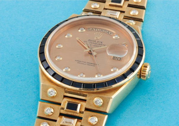 A very rare and attractive yellow gold, diamond and sapphire-set calendar quartz stone set bracelet watch with centre seconds and champagne dial