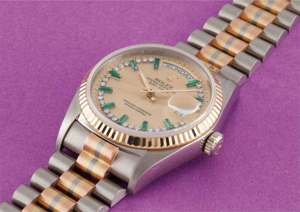 A very rare three color gold, diamond and emerald-set calendar wristwatch with bracelet, centre seconds and champagne dial