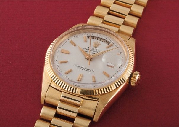 An extremely rare, early and historically interesting yellow gold calendar wristwatch with centre seconds, red date, bracelet and highly unusual German script dial
