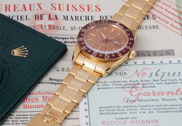 An exceptionally well preserved and most complete yellow gold dual time wristwatch with bracelet, bronze colored dial, and bakelite bezel, accompanied by presentation box and considerable documentation