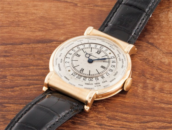 A fine and very rare yellow gold wristwatch with hooded lugs and world time indication