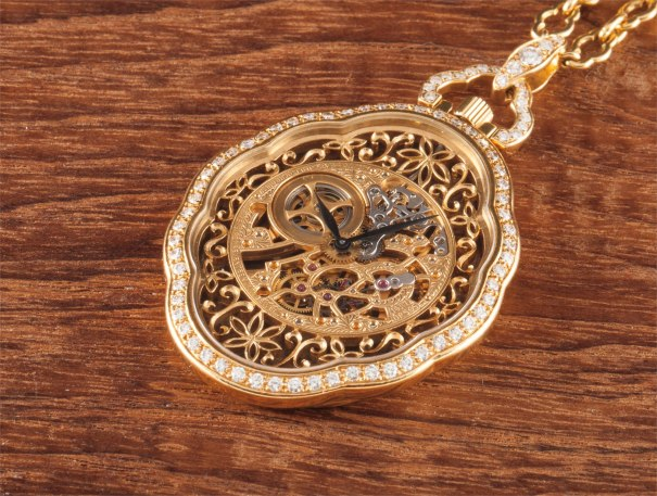 A fine and very rare yellow gold skeletonised and diamond set keyless lever watch and pendant