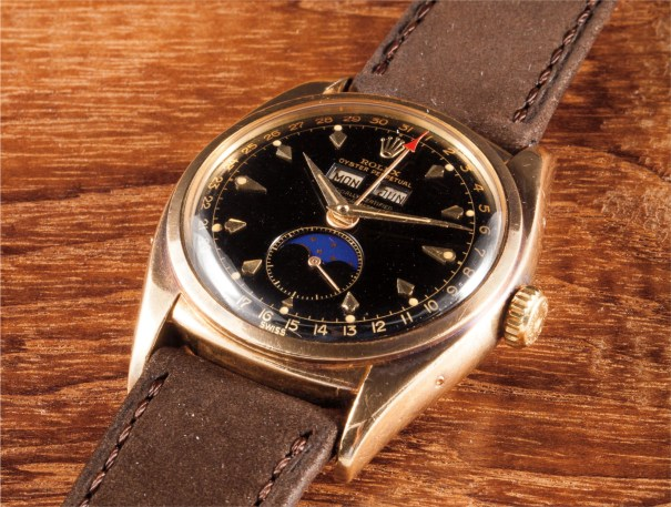 An extremely rare, historical and highly important yellow gold wristwatch with triple calendar, black lacquer dial, phases of the moon and original certificate, rating certificate and instruction manual