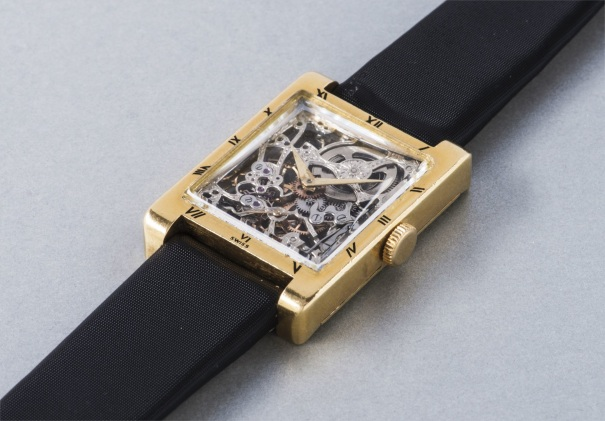 A very rare and elegant yellow gold rectangular skeletonized wristwatch with black enameled Roman numerals