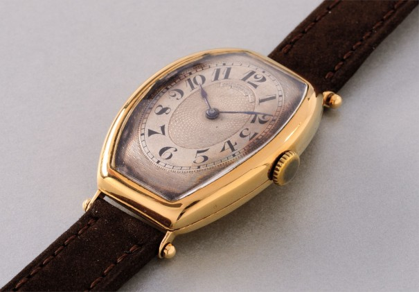 An extremely rare and elegant tonneau-shaped yellow gold wristwatch with hinged case