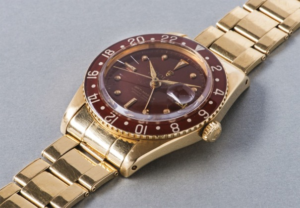 A rare and attractively preserved yellow gold dual time wristwatch with bracelet, brown colored dial and Bakelite bezel