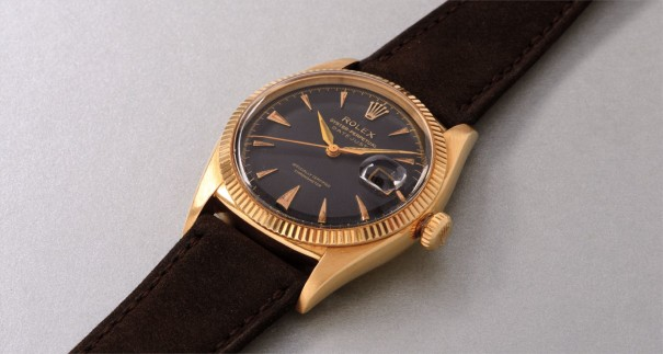 A rare and attractive yellow gold wristwatch with black dial and date