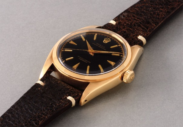 A rare and very attractive yellow gold wristwatch with black dial