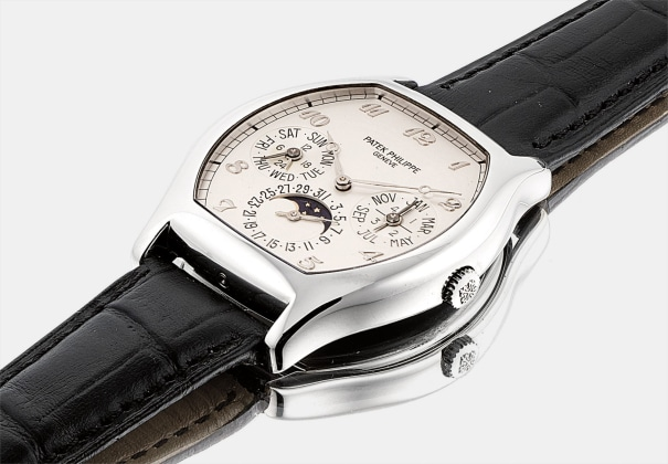 A fine and rare platinum tonneau-shaped perpetual calendar wristwatch with moon phases, 24 hours, leap year indicator and Breguet numerals