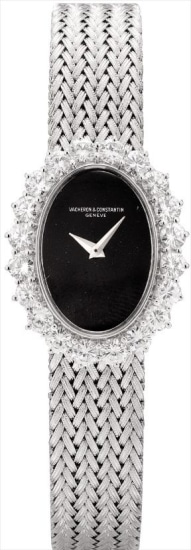 A lady's white gold and diamond-set oval bracelet watch with onyx dial