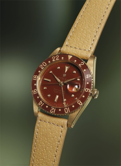 A fine and rare yellow gold dual time wristwatch with sweep center seconds, date, brown lacquer dial and bakelite bezel
