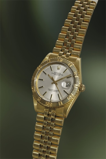 A highly rare and attractive yellow wristwatch with sweep center seconds, date, bracelet, revolving bezel, guarantee and fitted presentation box