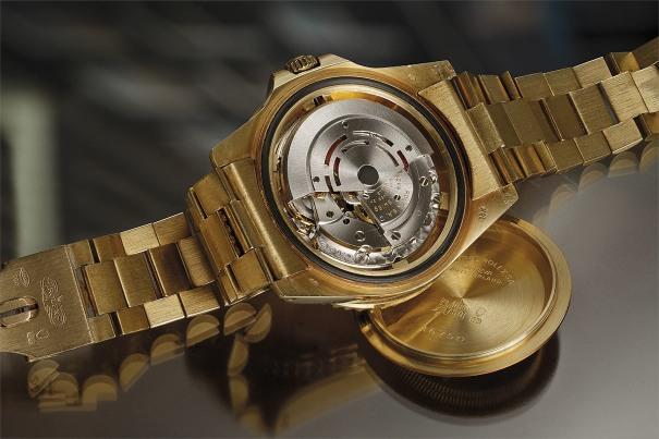 An extremely rare, important, and highly attractive yellow gold, sapphire, ruby and diamond‐set dual time wristwatch with diamond-set bracelet.