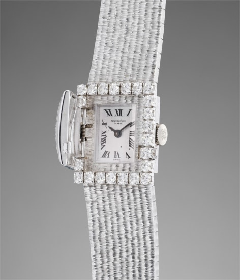 A very fine and extremely elegant white gold and diamond-set rectangular-shaped lady's bracelet watch with concealed dial and certificate