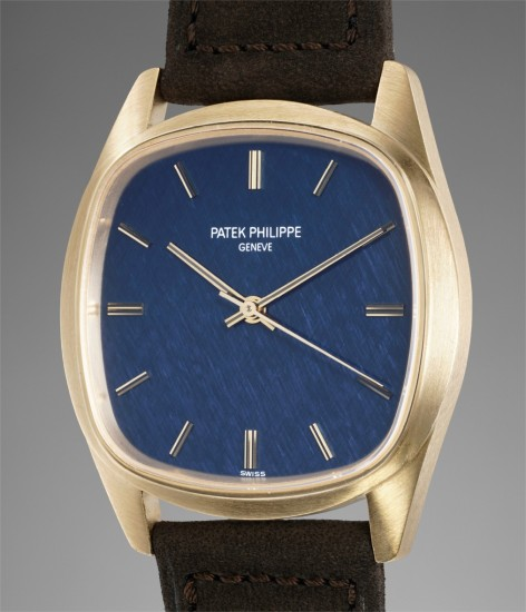 A fine and unusual yellow gold wristwatch with textured blue dial and winding crown on the back