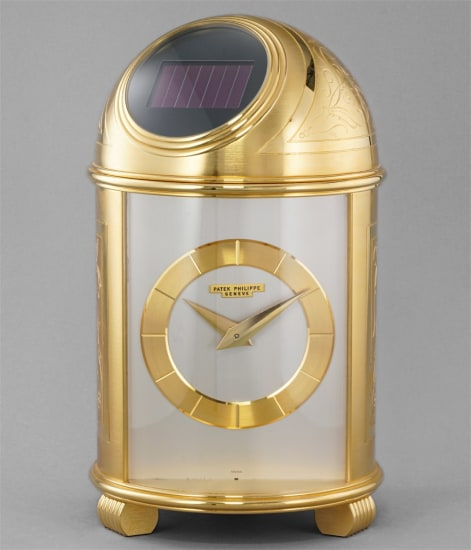 An extremely fine and rare engraved gilt brass solar powered dome table clock