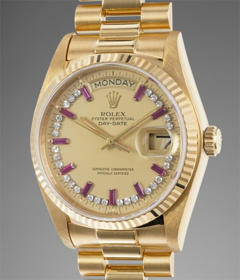 A rare and attractive yellow gold, diamond and ruby-set calendar wristwatch with center seconds, bracelet, champagne dial and box