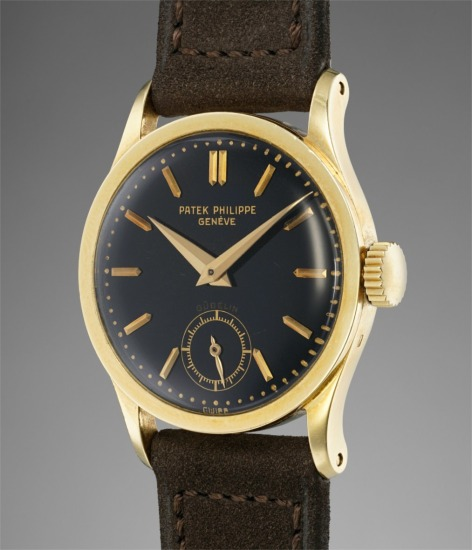 A fine, very rare, and extremely attractive yellow gold wristwatch with black dial, retailed by Gübelin