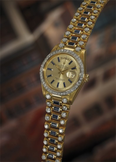An extremely rare, important, and impressive yellow gold, diamond and baguette sapphire-set calendar wristwatch with center seconds and bracelet.