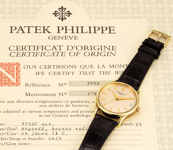 An attractive yellow gold wristwatch with date, center seconds and the certificate of origin