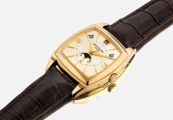 A fine and attractive yellow gold tonneau-shaped annual calendar wristwatch with center seconds and moonphase