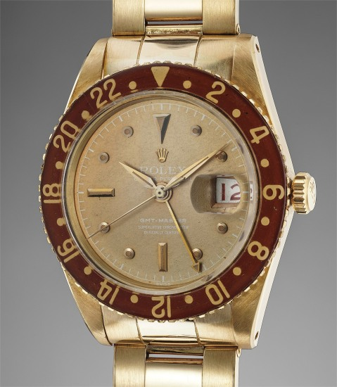 A fine, very rare and highly attractive yellow gold automatic dual time wristwatch with center seconds, date, champagne dial, bakelite bezel and contemporary aftermarket unsigned bracelet