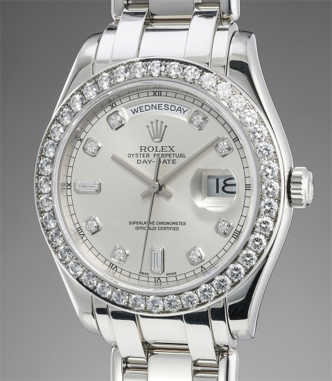 An extremely fine and very rare platinum and diamond-set automatic wristwatch with center seconds, date, day, bracelet, Guarantee and box