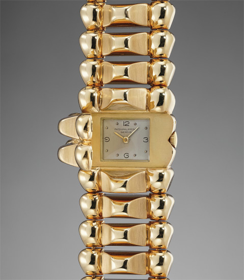 A lavish and heavy yellow gold bracelet watch with concealed dial