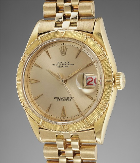 A rare, early and attractive yellow gold wristwatch with center seconds, roulette date wheel, rotating bezel and bracelet