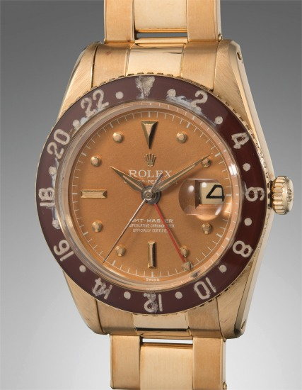 A very rare and exceptionally well-preserved yellow gold dual time wristwatch with bronze color dial, Bakelite bezel, and bracelet