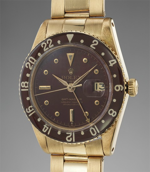 """A rare and attractive yellow gold dual time wristwatch """"exclamation mark"""" dial, with date, center seconds, Bakelite bezel and bracelet"""