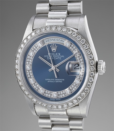 A rare and attractive platinum and diamond-set wristwatch with center seconds, blue dial, bracelet and service guarantee