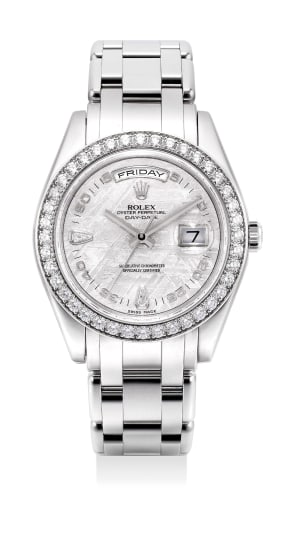 An extremely fine and very rare platinum and diamond-set wristwatch with meteorite dial, date and day display, bracelet, guarantee and presentation box