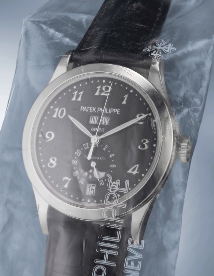 An elegant and attractive white gold limited edition automatic wristwatch with center seconds, annual calendar, 24-hour indication, inverted moonphases, black luminous dial with Breguet numerals, commemorative engraved back, certificate and box