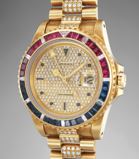 A highly attractive and exceptionally well-preserved yellow gold, diamond, ruby and sapphire-set dual time wristwatch with date and bracelet