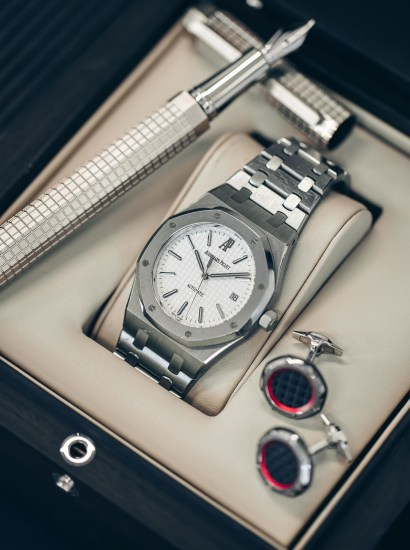 A superbly preserved and attractive stainless steel wristwatch with date, bracelet, original box, guarantee, cufflinks and fountain pen