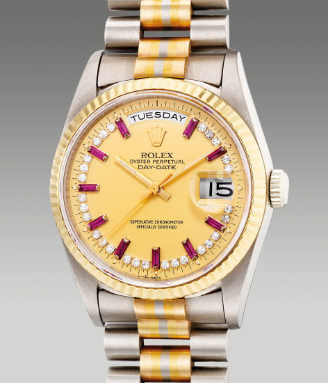 A very fine and rare two-tone white gold and yellow gold wristwatch with center seconds, day, date, ruby and diamond-set indexes and three color gold bracelet